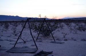 Old rusty swing set in the desert sunset