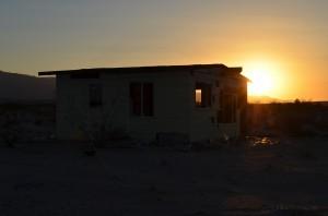 sunset behind a crumbling desert home
